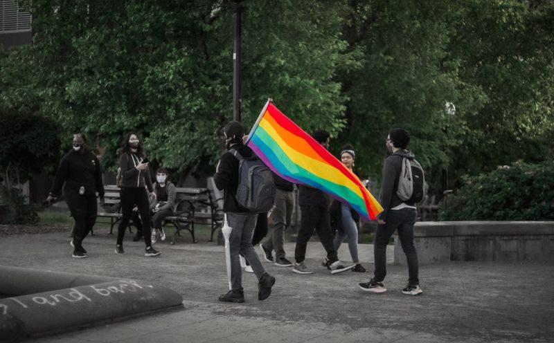 Capitol Hill, Seattle, WA, USA. A man holding a Pride flag walks through a park. Photo: Jake Schumacher/Unsplash