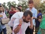 Assam flood: Congress MLA seen carrying relief materials on his back