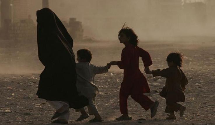 Image: UNAMA/Fraidoon Poya A family runs across a dusty street in Herat, Afghanistan. (file photo)
