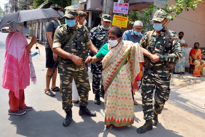 Security personnel help a aged woman at a polling station (Image Credit: UNI)