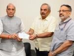 Rajnath Singh presenting a cheque to the Union Home Secretary