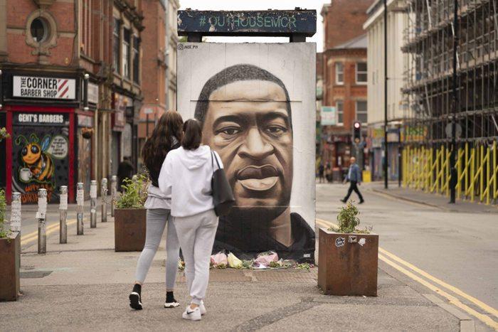 People gather by a mural of George Floyd in UK's Manchester