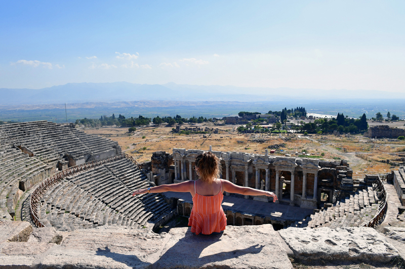 Turkey: A visitor sits on the ruins of the ancient city of Hierapolis