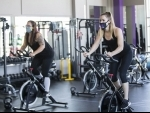 People wearing face masks exercise at a reopened fitness club in Barrie