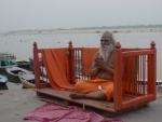 Sadhu meditates on banks of holy river of Ganges in Varanasi