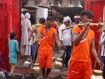 Devotees carrying holy water from the Ganges in Praygraj amid the ongoing Mal Maas