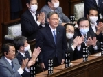 Yoshihide Suga (C) stands after being elected as Japans new prime minister in Tokyo