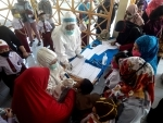 Indonesia: A health officer checks condition of an elementary student before giving a MR vaccine