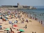 Portugal: Beachgoers sunbathe and swim in Carcavelos beach