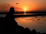 A local resident sits on the beach during sunset in Kuwait City