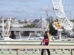 A woman wearing a face shield walks past the London Eye