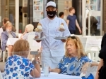 A waiter wearing a face mask serves a table at a restaurant in Vienna
