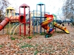 Children play in a park with Chinar leaves scattered all over in Kashmir