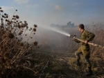 Israeli soldier tries to extinguish fire caused by explosive balloon