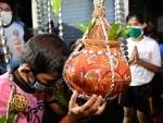 Boy wearing mask breaks earthen pot to mark Janmashtami