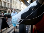 People wearing face masks pass by a statue of cow on a street in Lisbon