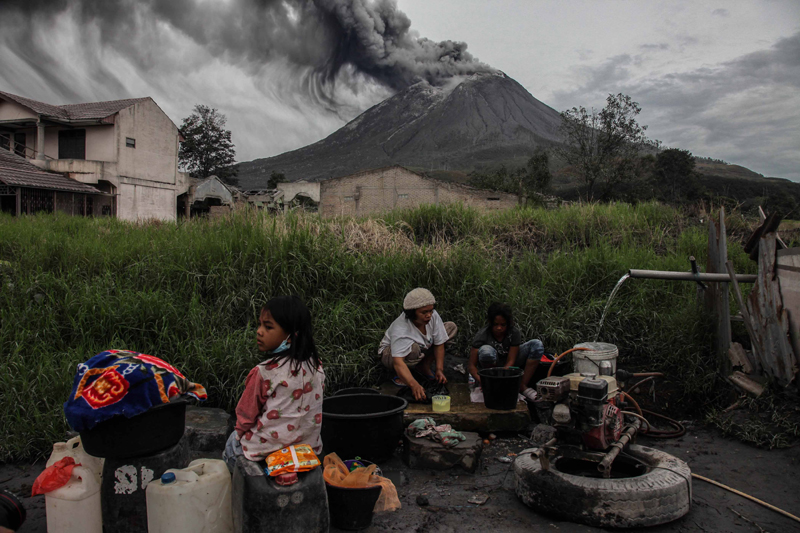 Indonesia: People wash their clothes as Mount Sinabung