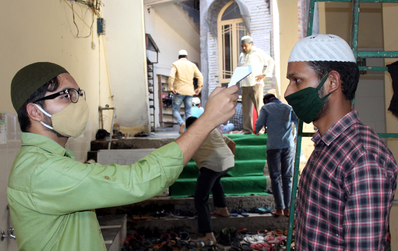 A person checks temperature of a Namazi as religious places opened Kullu district