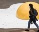 Pedestrian wearing mask walks by artwork in Sao Paolo