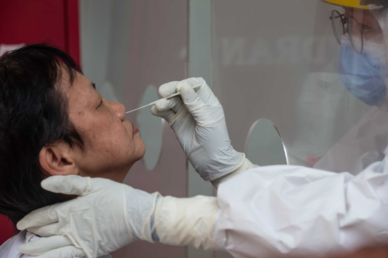 Jakarta: A medical worker takes a swab sample from a resident for COVID-19 tests