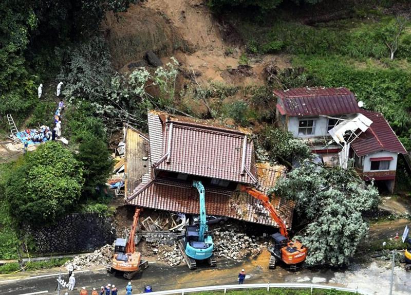 Japan: Excavators removing house damaged by a mudslide