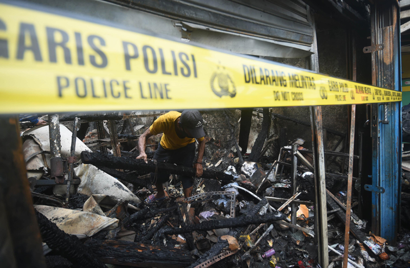 Indonesia: A resident looks for his belongings from a charred house