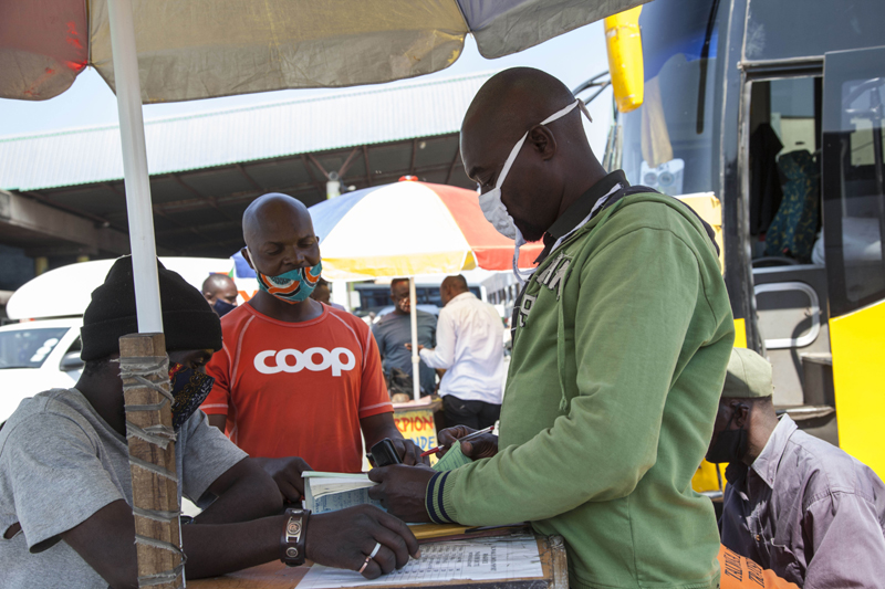 A passenger buys ticket for his trip at an intercity bus terminus in Lusaka