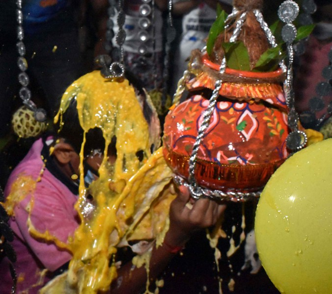 Boy wearing mask breaks earthen pot to mark Janmashtami