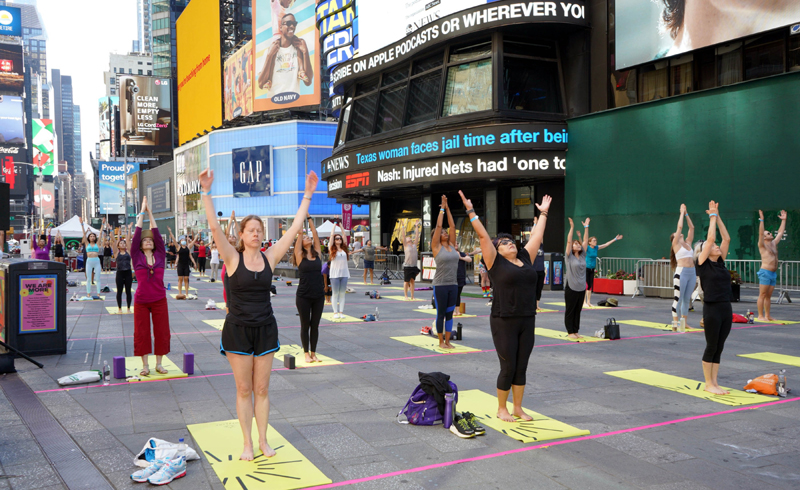 People practicing Yoga at Times Square