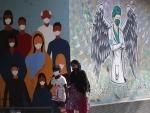 New Delhi: People walk past wall painting saluting COVID warriors