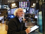 Traders work at the trading floor in the New York Stock Exchange