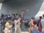 People climbing on a US Air Force aircraft at Kabul airport