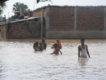 People braving floodwaters in a village near Patna