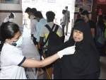 Health workers collect swab samples of passengers at Patna railway station