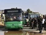 Local armed men are seen on buses in Daraa