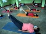 Students and volunteers of Tripura Yoga Association perform yoga