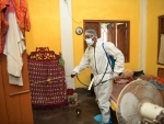 A volunteer sanitizing a house in Agartala