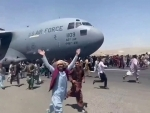 Glimpse of people running along US Air Force aircraft taking off from Kabul airport