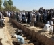 People digging graves for victims of a suicide explosion in Afghanistan's Kandahar city