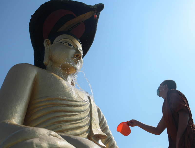 Buddhist monk cleaning statue of Lord Buddha at Agartala monastery