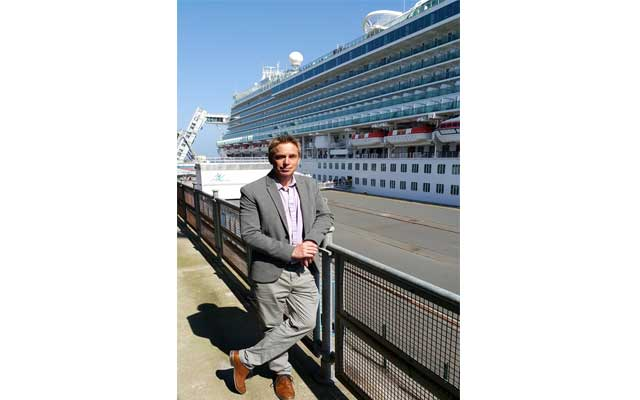 Cherbourg Tourisme Director Guillaume Hamel stands beside the massive Ventura Cruise Ship at the Cherbourg Cruise Terminal